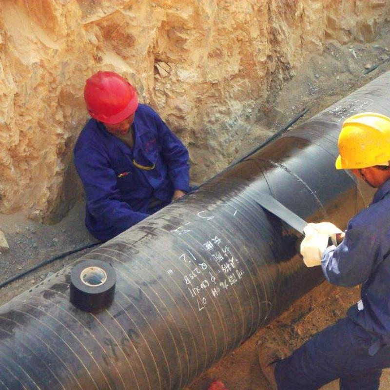 工人配合为直埋管道粘贴防腐胶带